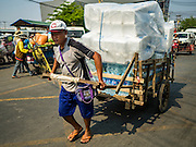 """15 FEBRUARY 2016 - ARANYAPRATHET, SA KAEO, THAILAND: A Cambodian porter in Aranyaprathet hauls a load of bottled water to the Cambodian side of the border. Thais selling bottled water in the border town of Aranyaprathet, opposite Poipet, Cambodia, have reported a surge in sales recently. Cambodian officials told their Thai counterparts that because of the 2016 drought, which is affecting Thailand and Cambodia, there have been spot shortages of drinking water near the Thai-Cambodian and that """"water shortages in Cambodia had prompted people to hoard drinking water from Thailand.""""     PHOTO BY JACK KURTZ"""