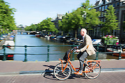 In Amsterdam rijdt een man in pak op een oranje fiets over de gracht.<br /> <br /> In Amsterdam a man in suit rides on an orange bike at the canals.