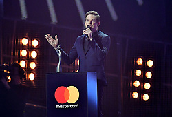 Michael C. Hall collects an award on behalf of David Bowie on stage at the Brit Awards at the O2 Arena, London.