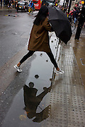 A woman jumps over a puddle after rainfall in Oxford Street, central London.