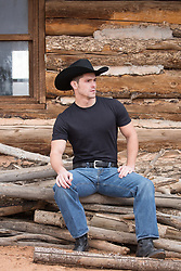 cowboy sitting on a pile of wood by a wooden cabin