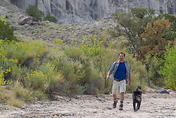 man on a hike in Abiquiu, New Mexico with his dog