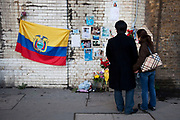 Couple read the details on a memorial to a Columbian man who was killed following a street fight on this spot on Southwark Street. December 2010. Cards, pictures and messages from friends adorn the wall.