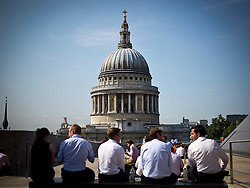 © Licensed to London News Pictures. 03/09/2012. LONDON UK. Office workers from the City of London enjoy the view of the dome of St Paul's Cathedral and the autumn sunshine during their lunch break. Photo credit : Andrew Baker/LNP