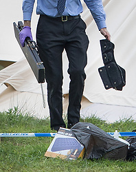 © Licensed to London News Pictures. 22/08/2017. London, UK. A police officer carries evidence that appears to be a chain (L) and a belt (R) at the Flamefest site near Tunbridge Wells in Kent where a man died and a woman was taken to hospital over the weekend. Over 200 people attended the adult sex festival with tickets costing £600 each. The incident  is currently being treated as unexplained. Photo credit: Peter Macdiarmid/LNP
