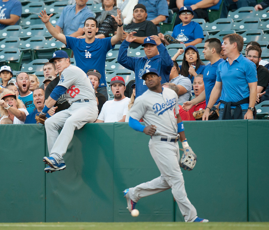 Dodger fans react after Chase Utley and Yasiel Puig can't come up with a could ball against the Angels Wednesday night at Angel Stadium.<br /> <br /> ///ADDITIONAL INFO:   <br /> <br /> angels.0519.kjs  ---  Photo by KEVIN SULLIVAN / Orange County Register  -- 5/18/16<br /> <br /> The Los Angeles Angels take on the Los Angeles Dodgers in inter-league play at Angel Stadium Wednesday night.