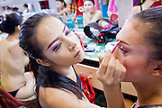 """Oct. 7, 2009 -- BANGKOK, THAILAND: """"Ladyboys"""" help each other put their makeup on backstage at the Mambo Cabaret in Bangkok, Thailand. The performers at the Mambo Cabaret in Bangkok, Thailand are all """"Ladyboys,"""" or kathoeys in Thai. Recognized as a third gender, between male and female, they are born biologically male but live their lives as women. Many kathoey realize they are third gender in their early teens, some only as old 12 or 13. Kathoeys frequently undergo gender reassignment surgery to become women. Being a kathoey in Thailand does not carry the same negative connotation that being a transgendered person in the West does. A number of prominent Thai entertainers are kathoeys. Photo by Jack Kurtz / ZUMA Press"""