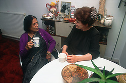 Carer and elderly woman drinking tea and talking at home,