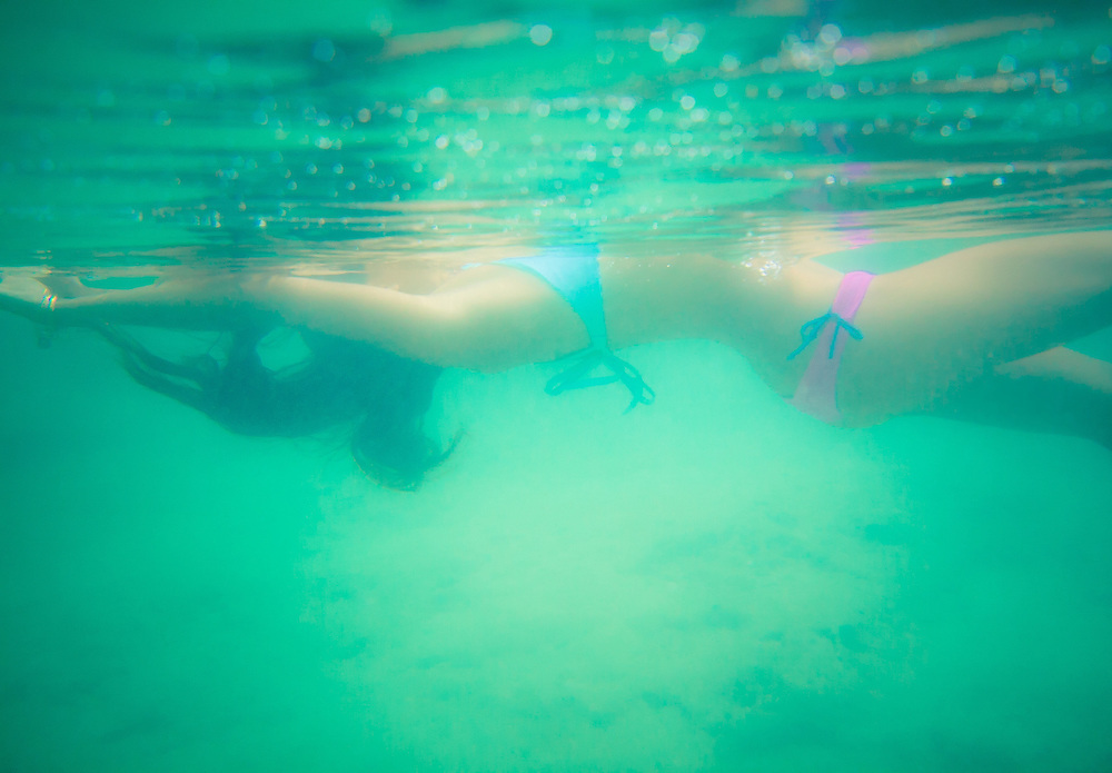 woman in a bikini floating underwater on a beach in hawaii