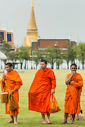 23 APRIL 2013 - BANGKOK, THAILAND:  Buddhist monks walk across Sanam Luang with the Grand Palace in the background. The palace has been the official residence of the Kings of Siam (and later Thailand) since 1782. The king, his court and his royal government were based on the grounds of the palace until 1925. The present monarch, King Bhumibol Adulyadej (Rama IX), currently resides at Chitralada Palace, but the Grand Palace is still used for official events. Several royal ceremonies and state functions are held within the walls of the palace every year. Construction of the palace began on 6 May 1782, at the order of King Buddha Yodfa Chulaloke (Rama I), the founder of the Chakri Dynasty, when he moved the capital city from Thonburi to Bangkok. Throughout successive reigns, many new buildings and structures were added, especially during the reign of King Chulalongkorn (Rama V). By 1925 the king, the Royal Family and the government were no longer permanently settled at the palace, and had moved to other residences. The palace complex is roughly rectangular and has a combined area of 218,400 square metres (2,351,000 sq ft), surrounded by four walls. It is situated on the banks of the Chao Phraya River at the heart of the Rattanakosin Island, today in the Phra Nakhon District. The Grand Palace is bordered by Sanam Luang and Na Phra Lan Road to the north, Maharaj Road to the west, Sanamchai Road to the east and Thai Wang Road to the south. The Grand Palace is made up of numerous buildings, halls, pavilions set around open lawns, gardens and courtyards. Its asymmetry and eclectic styles are due to its organic development, with additions and rebuilding being made by successive reigning kings over 200 years of history. It is divided into several quarters: the Temple of the Emerald Buddha; the Outer Court, with many public buildings; the Middle Court, including the Phra Maha Monthian Buildings, the Phra Maha Prasat Buildings and the Chakri Maha Prasat Buildings; the Inner Cou
