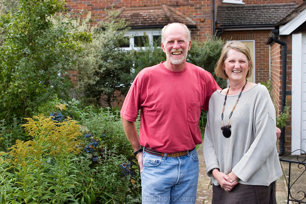 Richard and Fenella Hodson in front of their house, Godalming, UK. (Material World Family from Great Britain UK).
