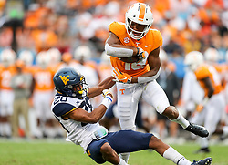 Sep 1, 2018; Charlotte, NC, USA; Tennessee Volunteers defensive back Nigel Warrior (18) returns a kickoff and breaks a tackle from West Virginia Mountaineers cornerback Keith Washington (28) during the third quarter at Bank of America Stadium. Mandatory Credit: Ben Queen-USA TODAY Sports