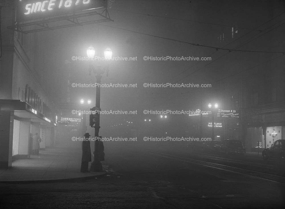 """Y-480130-01.  Night view of fog at SW 5th & Oak, January 30 1948. Published the next day as """"Homeward bound Portland traffic Friday night was slowed by the fog blanket which the weather bureau reported extending from Kelso, Wash., on the north to Salem on the south. Photographer's camera points south along S. W. 5th avenue at Oak in this picture, made at about 6:30 P. M."""" page 4."""