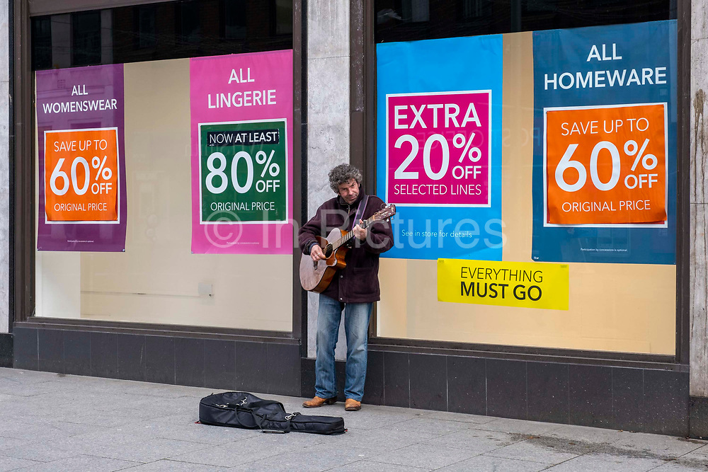 A busker singing outside the Folkestone Debenhams store in the final few days of the 'Everything Must Go' sale before closing down on 13th Jauary 2020 in Folkestone, Kent. United Kingdom. The company announced the closure of 19 stores across the UK after going into administration in 2019.