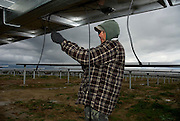 Workers fit electrical plugs on the last rows of panels, on the almost finished world?s largest solar power plant.