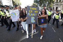 © Licensed to London News Pictures. 20/09/2019. London, UK. Activists taking part in the Global Climate Strike demonstration hold placards in front of a line of police blocking the road near Trafalgar Square. Thousands of similar actions are taking place all over the UK and the rest of the world. Photo credit: Peter Macdiarmid/LNP