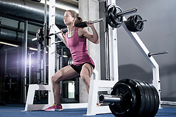 Mid adult woman doing squats barbell on her shoulders in the gym, Bavaria, Germany