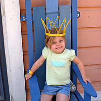 Europe, Scandinavia, Finland, Porvoo. A young girl seats herself on a throne under a crown of Swedish national colors.