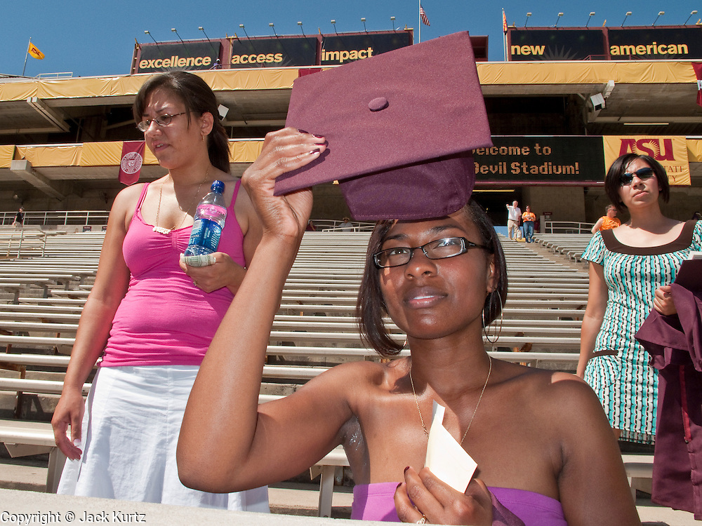 158834 ObamaASU0514 -- 13 MAY 2009 -- TEMPE, AZ:  Bianca Taswell (CQ) a Social Work major, uses her mortarboard as a sun shade in the stadium before graduation. She said she thought she was going to have a job after graduating, but just learned the position is frozen because of the economy.  President Barack Obama addressed the Arizona State University class of 2009 during the commencement program in Sun Devil Stadium in Tempe Wednesday evening.    ARIZONA REPUBLIC PHOTO BY JACK KURTZ