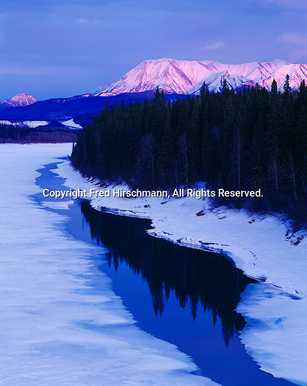 Sunset illuminating Mount Prudence beyond the Liard River during spring break-up, British Columbia, Canada.
