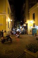 People whizz through the narrow cobblestone streets in historic Macau surrounded by old Portuguese colonial buildings