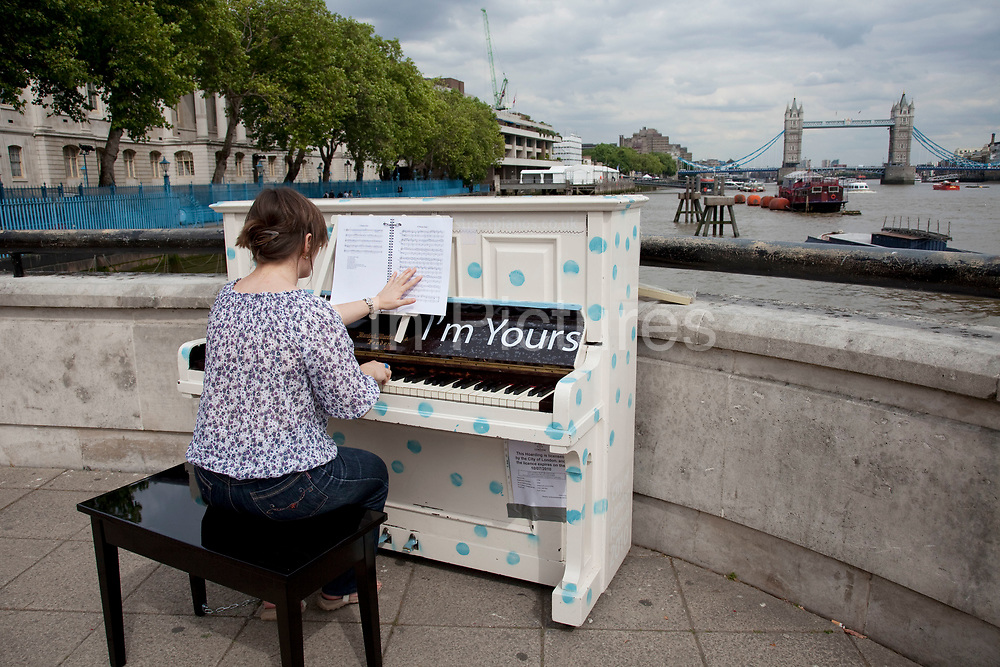 """Piano art project by the Thames. More than 30 pianos are placed around the capital for members of the public to enjoy and play. As part of the Sing London festival, organisers hope people will tinkle on the ivories and share their favourite tunes with strangers. The pianos marked """"Play me, I'm yours"""", will be dropped in locations all accross London. The project is being put together with the help of artist Luke Jerram, with each of the 31 pianos getting a themed makeover based on its location."""