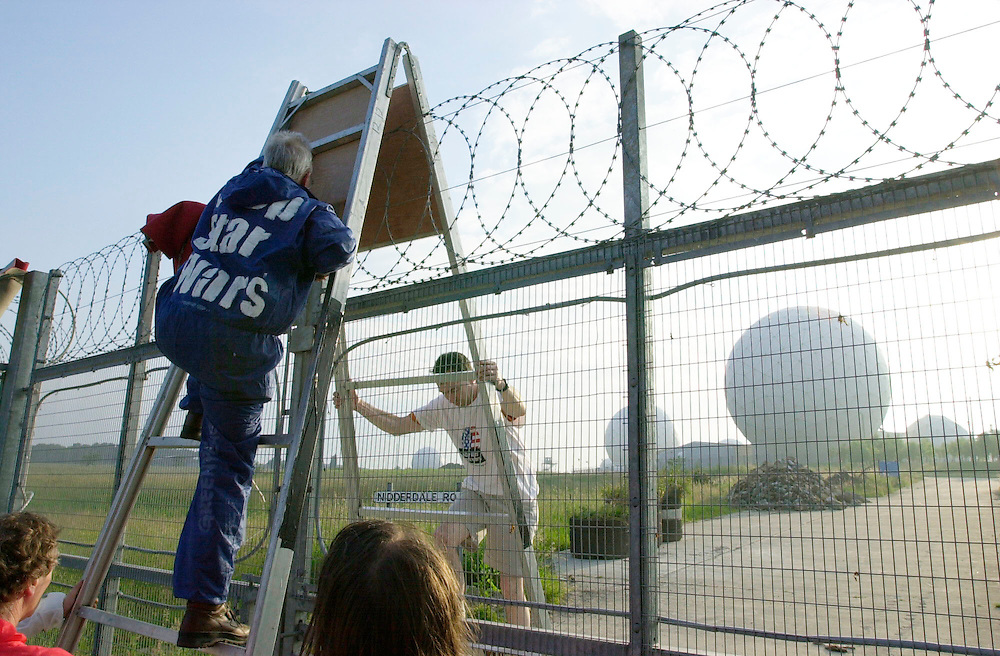 """Activists climbing over ladder which has been placed over barbed wire fence. """"Golfballs"""" visible in background.  Bush plans to use the Menwith base as his """"eyes and ears"""" for the Star Wars defense system. Bush can't install the system without Blair's approval. Accession #: 3.0093.001.02"""