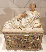 Etruscan cinerary urn depicting a young male figure and a frieze showing a battle scene. 3rd Century BC