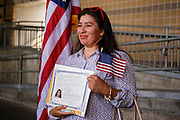 17 SEPTEMBER 2020 - DES MOINES, IOWA: SILVIA GUADALUPE GANUZA, originally from El Salvador, holds her naturalization certificate as she poses for pictures next to the American flag after a naturalization ceremony at Principal Park, a minor league baseball stadium in downtown Des Moines. About 75 people from 32 countries were naturalized as US citizens Thursday. It was the last citizenship ceremony in Des Moines before citizenship fees dramatically increase. Starting Oct. 2, the fee to apply for U.S. citizenship will increase from $640 to $1,160 if filed online, or $ 1,170 in paper filing, a more than 80% increase in cost. Advocates for immigration are afraid the new fees will be too expensive for many immigrants and say it's an effort by the Trump Administration to limit the number of new citizens welcomed into the United States. Because of the COVID-19 pandemic, there has been dramatic slow down in the number of naturalization ceremonies this year.          PHOTO BY JACK KURTZ