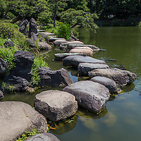 """Kiyosumi Teien Garden was the site of the residence of the Edo Period business magnate, Kinokuniya Bunzaemon. Later it became the residence of the Edo of the Lord of Sekiyado castle, Shimofusa-no-kuni the period when the basic form of the garden came into existence. In 1878, Iwasaki Yataro, chose this property to use a garden for the entertainment of important guests. After the design and construction phases ended, the garden opened in 1880 under the name of """"Fukagawa Shimbokuen."""" In later years, the waters of the Sumida River were brought into the grounds to make the pond. Hills and waterless waterfalls were constructed and famous rocks from all over Japan were brought in to embellish the garden. The garden was completed in the Meiji Period and developed into a famous strolling garden centered around a large pond."""