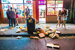 © Licensed to London News Pictures . 27/12/2017. Wigan, UK. Rubbish accumulates by a bin outside takeaways. Revellers in Wigan enjoy Boxing Day drinks and clubbing in Wigan Wallgate . In recent years a tradition has been established in which people go out wearing fancy-dress costumes on Boxing Day night . Photo credit: Joel Goodman/LNP