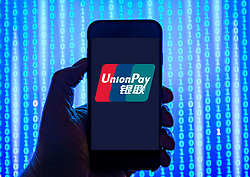 Person holding smart phone with UnionPay logo displayed on the screen. UnionPay fis a Chinese financial services corporation EDITORIAL USE ONLY