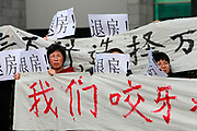 Home buyers who have made down payments on properties at China Vanke Co.'s Qinglinjing development protest with signs requesting refunds outside the Vanke Shanghai Center, in Shanghai, China, on Wednesday, Nov. 23 2011. A portion of home owners across the country are unhappy as government restrictions on real estate speculations have caused their newly purchased homes to fall in value, a majority of the homes in this case are yet to be completed.
