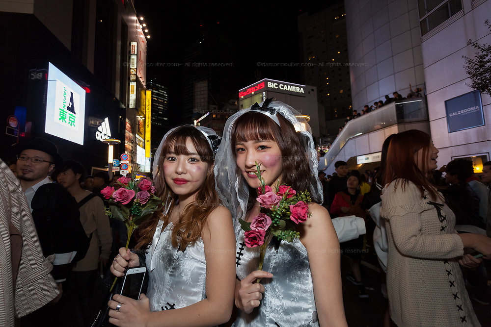 Two young Japanese women dressed as brides during the Halloween celebrations in Shibuya, Tokyo, Japan. Wednesday October 31st 2018 .  Halloween has grown massively popular  in Japan over the last few yers. Primarily an event for young adults who use it as a chance to dress up in inventive costumes and spend the night partying . In recent years the misbehaviour of some revellers has caused a heavier police presence on the street and  a push back from the Japanese society, and media  who see no need for nor benefits to this western cultural import.