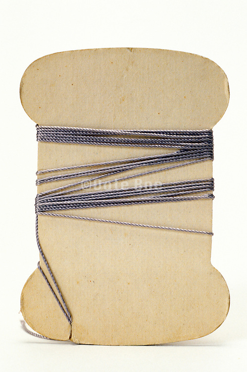 a flat carton spool with little thread still on it