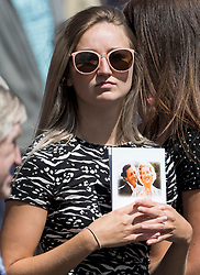 © Licensed to London News Pictures. 10/07/2020. London, UK. A woman holds an order of service with a picture of Dame Vera Lynn on the cover, as members of the public gather in the town of Ditchling, East Sussex, to pay their respects ahead of the funeral of Dame Vera Lynn. The 'Forces' Sweetheart', who died last month aged 103, was famous for singing performances during WW2, which helped raise morale amongst troops abroad. Photo credit: Ben Cawthra/LNP