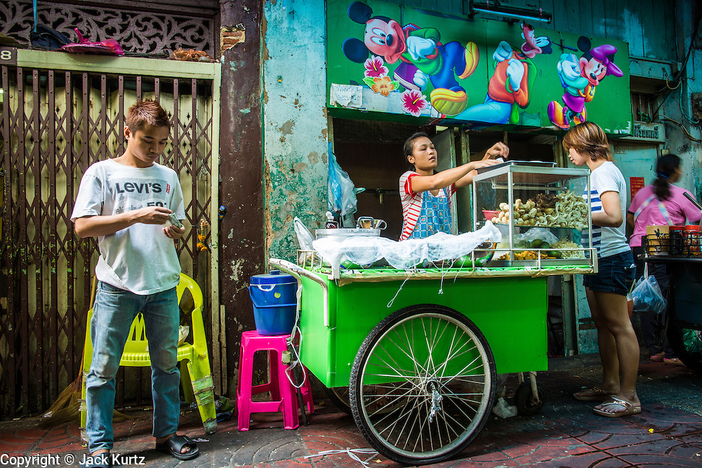 """01 MARCH 2013 - BANGKOK, THAILAND: People buy food at a street food stall in Bangkok's Chinatown district. Thailand's economic expansion since the 1970 has dramatically reduced both the amount of poverty and the severity of poverty in Thailand. At the same time, the gap between the very rich in Thailand and the very poor has grown so that income disparity is greater now than it was in 1970. Thailand scores .42 on the """"Ginni Index"""" which measures income disparity on a scale of 0 (perfect income equality) to 1 (absolute inequality in which one person owns everything). Sweden has the best Ginni score (.23), Thailand's score is slightly better than the US score of .45.    PHOTO BY JACK KURTZ"""