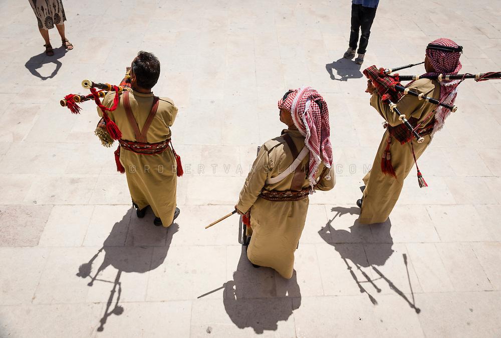 Tourists looking at bagpipe players in the South Theatre at the Jerash Ruins, Jerash, Jordan. Photo © Robert van Sluis