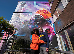 "© Licensed to London News Pictures; 02/04/2021; Bristol, UK. JEN REID and her husband ALASDAIR DOGGART in front of ""United Souls United Goals"", an artwork by artist Mr Cenz, of a giant mural of Jen Reid, the woman who stood on the plinth of the statue of Edward Colston after it was torn down at a Black Lives Matter protest in Bristol in 2020 and of whom a statue was made and temporarily placed on the plinth. The mural is on the wall by The Canteen on Stokes Croft directly opposite Banksy's Mild Mild West mural, and replaces an earlier mural of Breakdancing Jesus. The mural is launched by The Bristol Eighteen and has the welcoming message ""Rise up Bristol, stand tall... Bristol's a city for all"" by poet Lawrence Hoo with Bristol's own street artist Inkie lending a hand to convey Lawrence Hoo's open-arms message of togetherness. The piece has been created to commemorate the Black Lives Matter protest in Bristol on June 7th 2020 and promote the ongoing global anti-racism movement. The Bristol Eighteen was formed, in the wake of the removal of Edward Colston's statue, to create a vehicle to raise funds for anti-racist educational organisations. Photo credit: Simon Chapman/LNP."