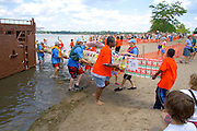 Volunteers carry milk carton canoe from Lake Calhoun to compactor truck. Aquatennial Beach Bash Minneapolis Minnesota USA