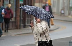 ©Licensed to London News Pictures 30/10/2020  <br /> Sevenoaks, UK. A lady crossing the road holding onto her umbrella. The October wet weather continues today for shoppers in Sevenoaks High Street in Kent. The Met office has issued a weather warning for parts of the UK for heavy rain and strong winds which could bring some flooding. Photo credit:Grant Falvey/LNP
