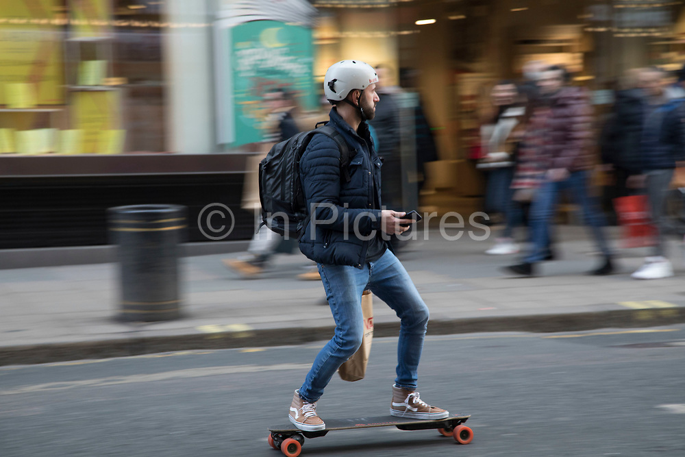 Man on an smartphone controlled electric skateboard in London, England, United Kingdom.