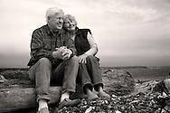 seniors sitting on beach log toghether