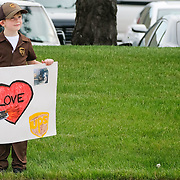 Colton Wigfield, 6, of Sylvania, is dressed like a driver while holding a sign as he waits to see his stepdad drive by at the United Parcel Service facility in Maumee, Ohio, on Friday, May 15, 2020. UPS drivers were led out by police and with supporters cheering them on as they went out on their routes. THE BLADE/KURT STEISS