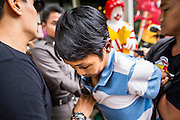 "31 MAY 2014 - BANGKOK, THAILAND: A young man is led away by Royal Thai Police after he walked down a sidewalk holding a sign that said ""Respect my vote"" in a solitary protest against the military government. Bangkok was mostly quiet Saturday. There were only a few isolated protests against the coup and military government.    PHOTO BY JACK KURTZ"