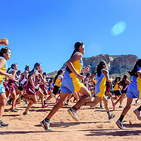 The girls varsity take to the course beneath Dowa Yalanne at the Zuni Invitational cross country meet in Zuni Saturday.