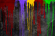 Colour paint drips down a black wall