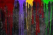Colour paint drips down a black wall