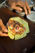 """A Paan wallah making paan in Old Delhi, India. <br /> Paan consists of chewing Betel leaf (Piper betle) combined with the areca nut. It is chewed as a palate cleanser and a breath freshener. It is also commonly offered to guests and visitors as a sign of hospitality and as an """"ice breaker"""" to start conversation. It also has a symbolic value at ceremonies and cultural events in south and southeast Asia. Paan makers may use mukhwas or tobacco as an ingredient in their paan fillings. Although most types of paan contain areca nuts as a filling, some do not. Other types include what is called sweet paan, where sugar, candied fruit and fennel seeds are used."""