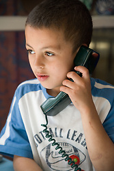 Boy using telephone,